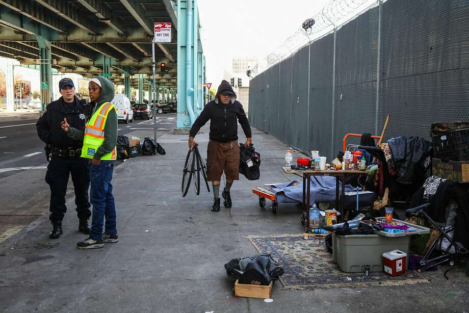 Larry Muraoka, a homeless man, packs up his belongings as police and a Department of Public Works employee assess the situation on Division Street in San Francisco in March 2. Photo: Gabrielle Lurie, Special To The Chronicle