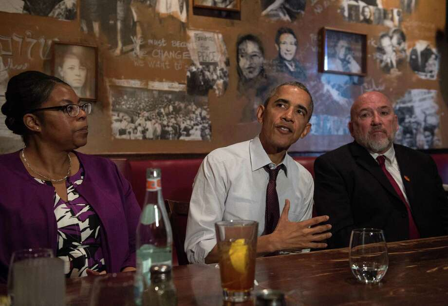 President Barack Obama, with Ramona Brant (left) and Phillip Emmert, meets at Busboys and Poets in Washington with former prisoners whose previously received commutations. Photo: Nicholas Kamm /Getty Images / AFP or licensors