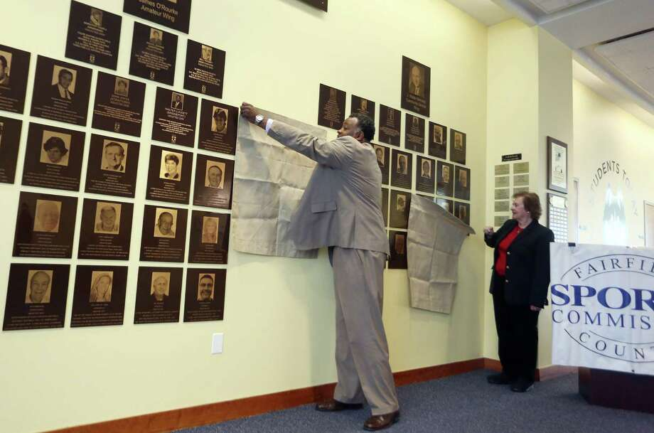 Lambert Shell, left, and Angela Tammaro unveil their plaques for the 2015 Fairfield County Hall of Fame inside of the UConn Stamford campus on Wednesday, March 30, 2016. Photo: Michael Cummo / Hearst Connecticut Media / Stamford Advocate