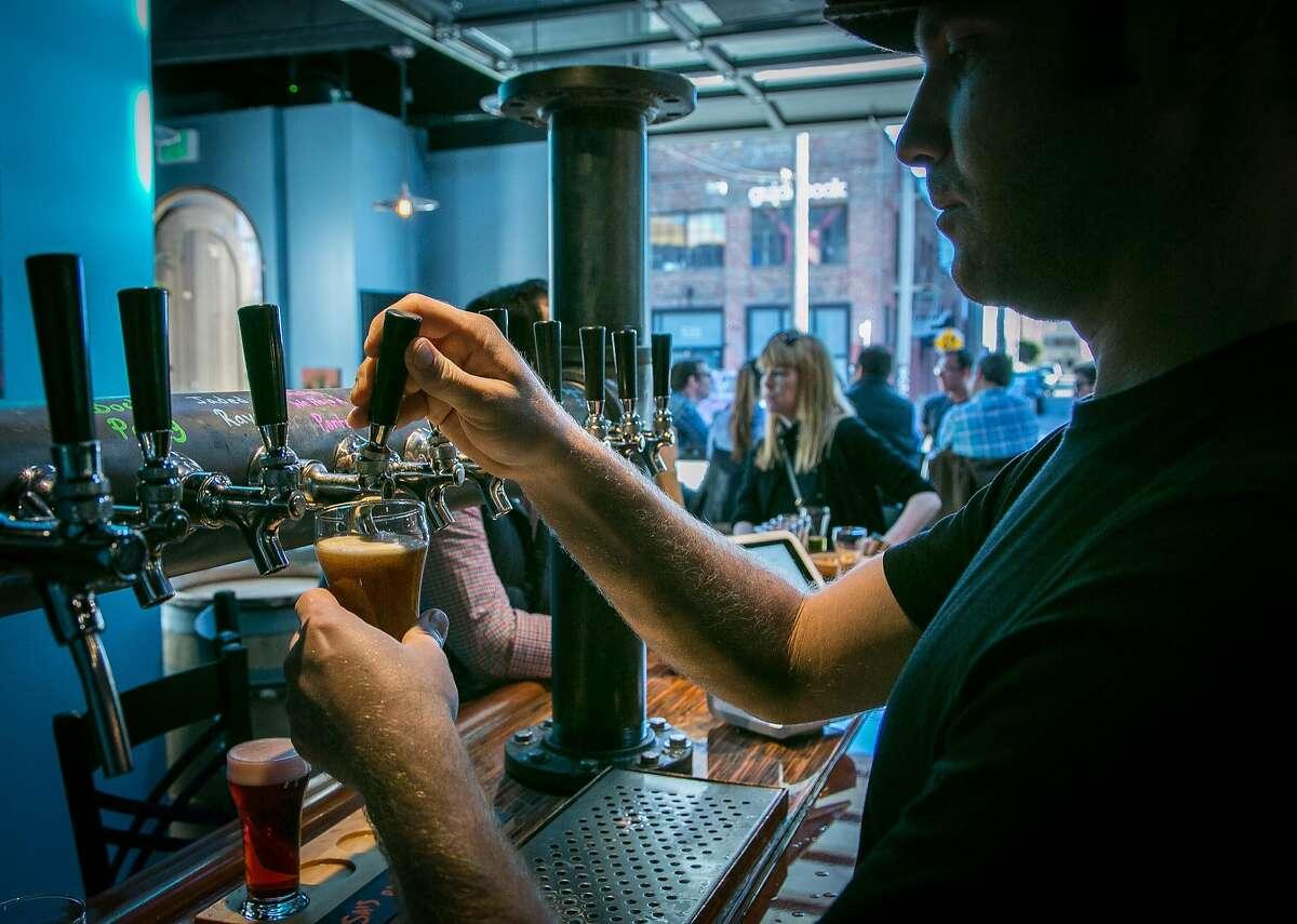 Bartender Tyler Miller pours a beer at Black Hammer Brewing in San Francisco, on Sunday, October 18th, 2015.