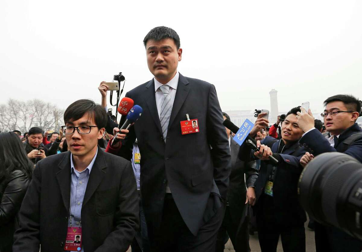 China's former basketball player and CPPCC representative Yao Ming, center, is chased by journalists as he arrives at the Great Hall of the People to attend the opening session of the Chinese People's Political Consultative Conference (CPPCC) in Beijing, Thursday, March 3, 2016. The more than 2,000 members of China's top legislative advisory body convened their annual meeting Thursday, kicking off a political high season that will continue with the opening of the national congress on Saturday. (AP Photo/Andy Wong)