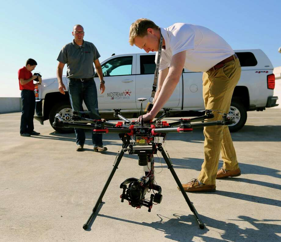 Midstream Integrity intern Sam Owens prepares an octocopter for flight Wednesday Sept. 23, 2015, under supervision from chief pilot Thomas Zaremba, center, while lead engineer Frank Hurtado prepares the controllers in the background. Midstream Integrity is an FAA-approved drone service provider specializing in the oil and gas industry services. Photo: William Luther, Staff / San Antonio Express-News / © 2015 San Antonio Express-News