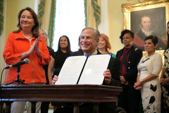 Texas Gov. Greg Abbott, joined by his wife, Cecilia, holds up the executive ordering announcing the expansion of the Governor's Commission for Women during a news conference at the Governor's mansion in Austin, Texas, on Wednesday, March 30, 2016. (Deborah Cannon/Austin American-Statesman via AP)