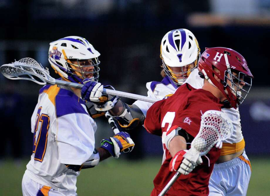 UAlbany's Seth Oakes, left, and Bennett Drake defend Hartford's Sean Mahon during their college lacrosse on Wednesday March 30, 2016 in Albany, N.Y. (Michael P. Farrell/Times Union) Photo: Michael P. Farrell / 10036023A