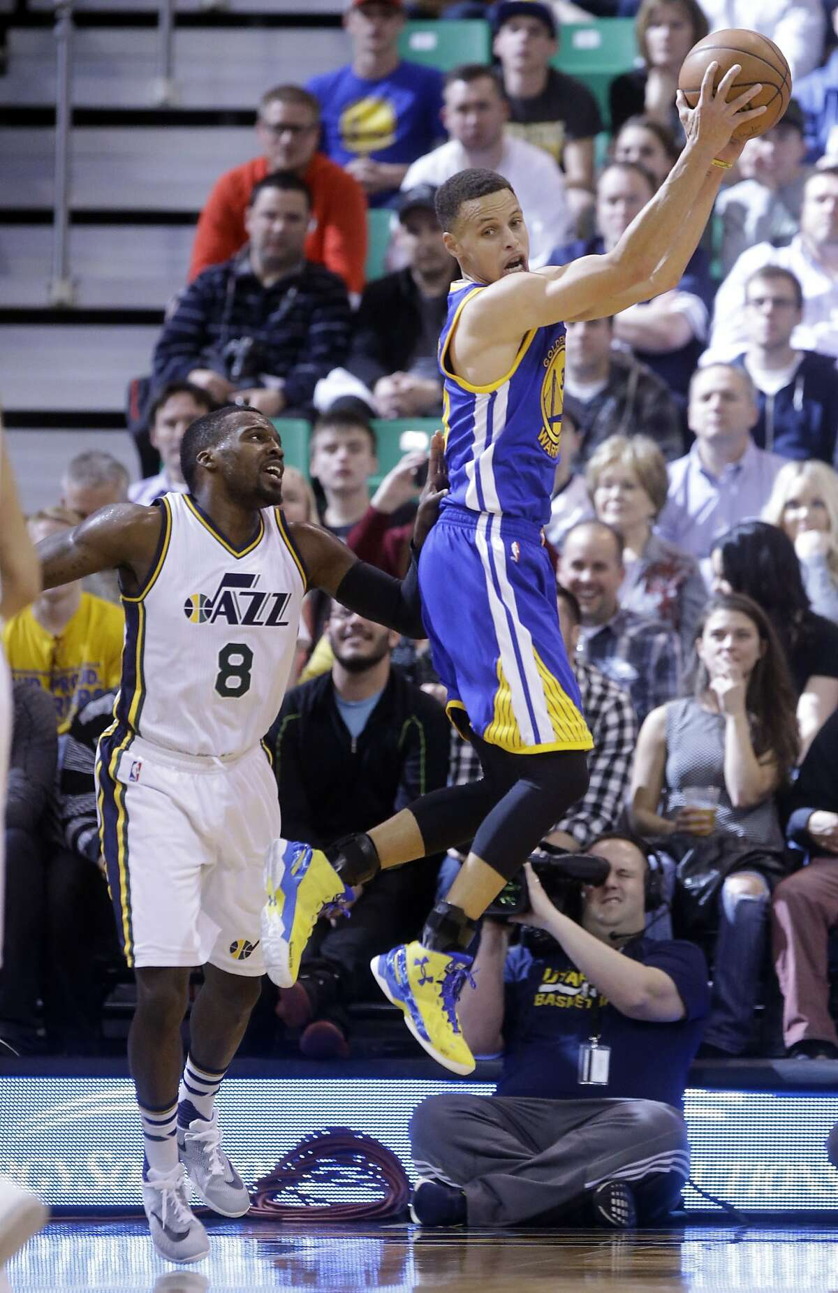 Golden State Warriors guard Stephen Curry (30) catches a pass while Utah Jazz guard Shelvin Mack (8) looks on during the first quarter of an NBA basketball game Wednesday, March 30, 2016, in Salt Lake City. (AP Photo/Rick Bowmer)