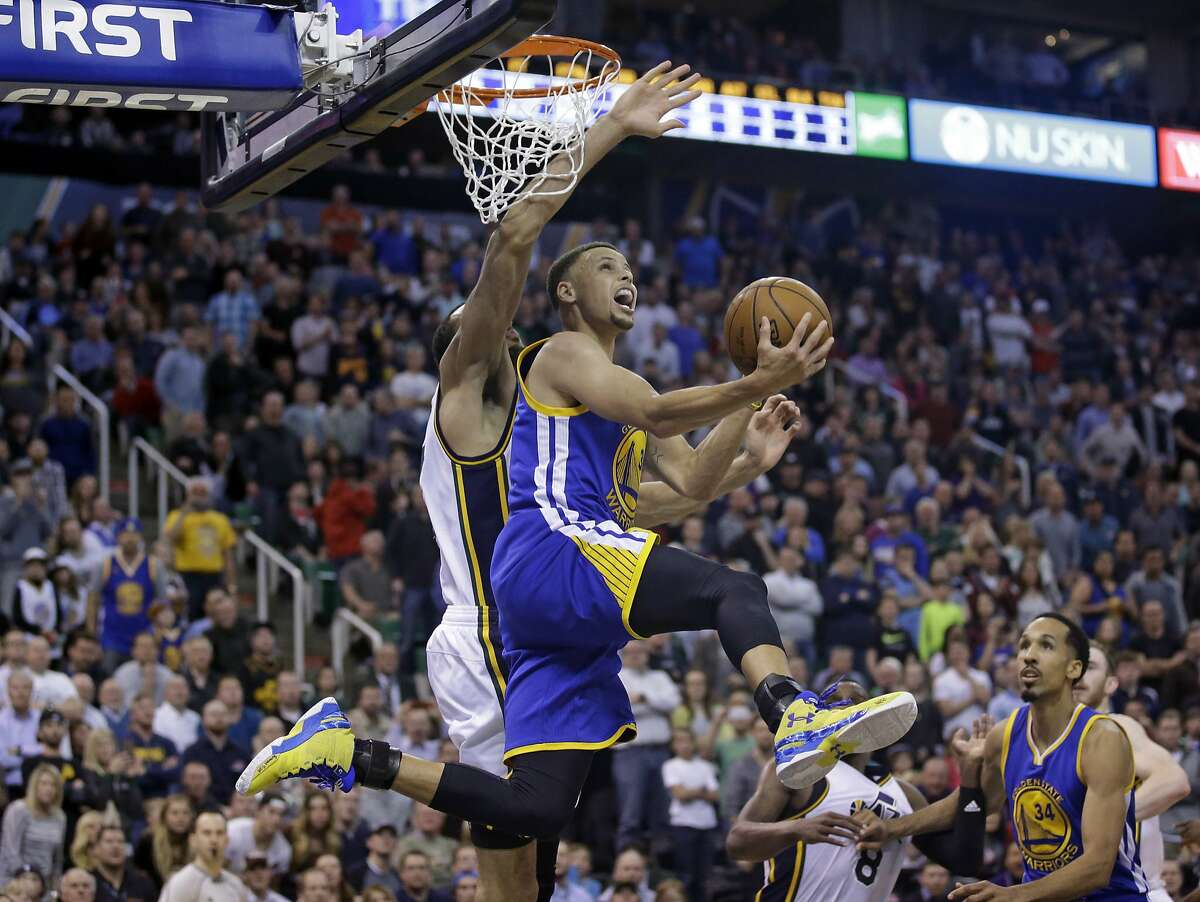 Golden State Warriors guard Stephen Curry (30) lays the ball up as Utah Jazz center Rudy Gobert, rear, defends during the second half of an NBA basketball game Wednesday, March 30, 2016, in Salt Lake City. The Warriors won 103-96 in overtime. (AP Photo/Rick Bowmer)