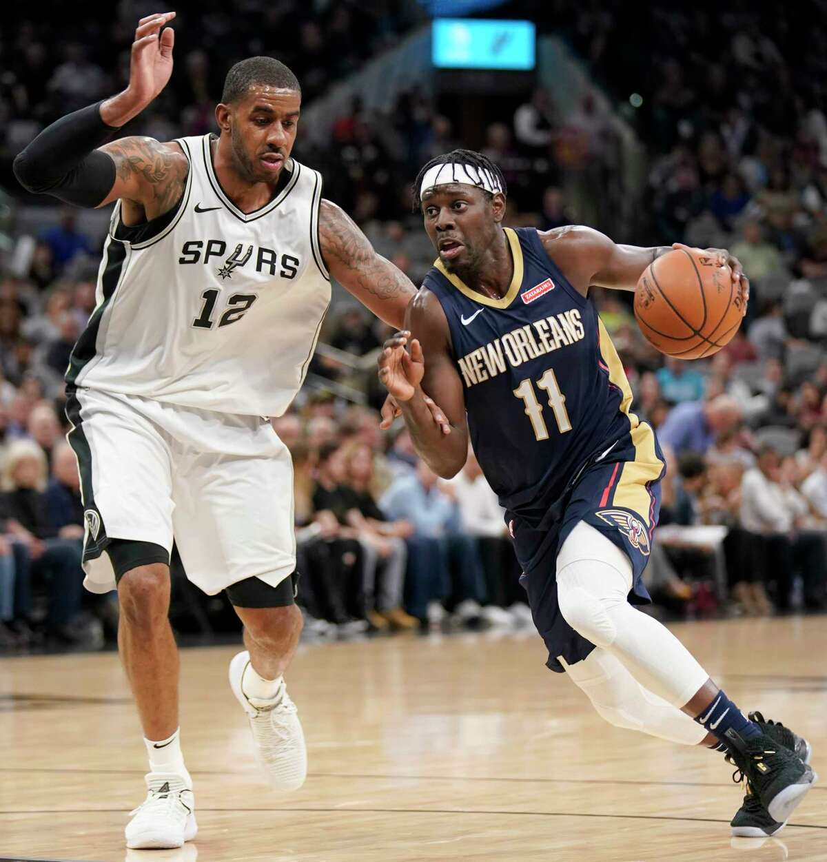 New Orleans Pelicans' Jrue Holiday (11) drives past San Antonio Spurs' LaMarcus Aldridge during the first half of an NBA basketball game, Thursday, March 15, 2018, in San Antonio. (AP Photo/Darren Abate)