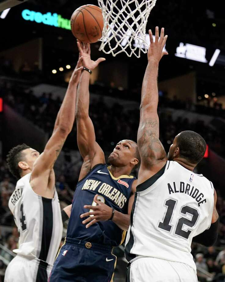 New Orleans Pelicans' Rajon Rondo, center, shoots against San Antonio Spurs' LaMarcus Aldridge (12) and Danny Green during the first half of an NBA basketball game, Thursday, March 15, 2018, in San Antonio. (AP Photo/Darren Abate) Photo: Darren Abate, Associated Press / FR115 AP