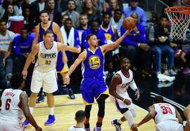 DeAndre Jordan, Blake Griffin, Chris Paul and Jamaal Crawford of the Los Angeles Clippers watch as Steph Curry of the Golden State Warriors scores during their NBA game in Los Angeles, California on November 19, 2015. AFP PHOTO / FREDERIC J. BROWNFREDERIC J. BROWN/AFP/Getty Images
