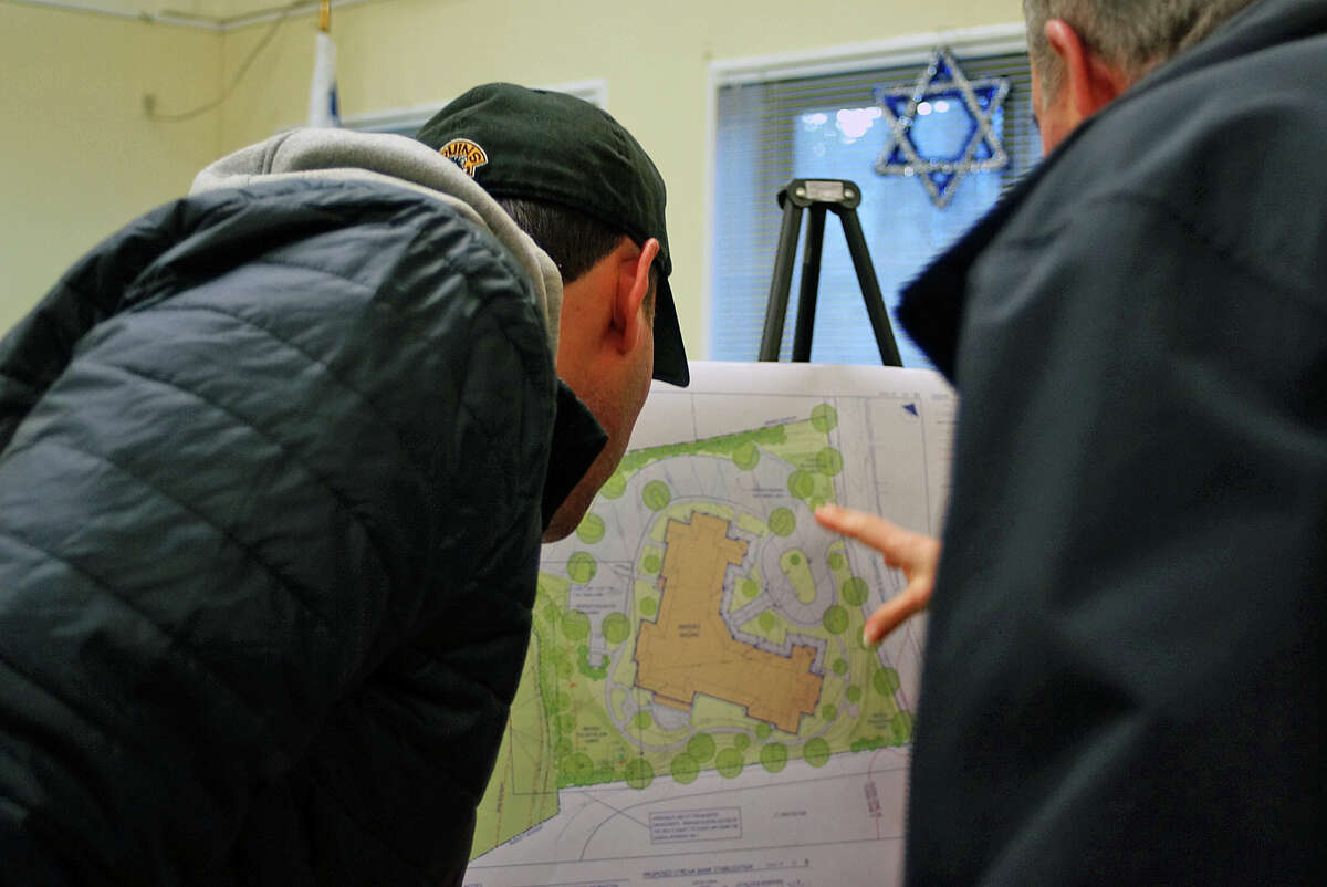 Neighbors check out the site plan for a proposed assisted living facility for property on Stratfield Road, now home to a synagogue.