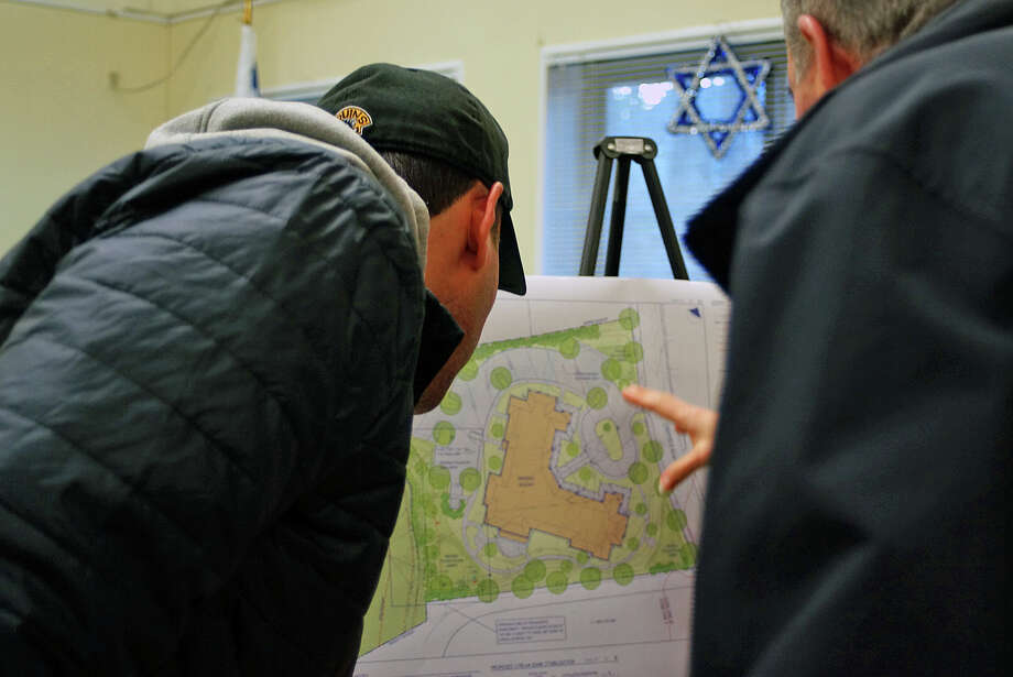 Neighbors check out the site plan for a proposed assisted living facility for property on Stratfield Road, now home to a synagogue. Photo: Genevieve Reilly / Hearst Connecticut Media / Fairfield Citizen