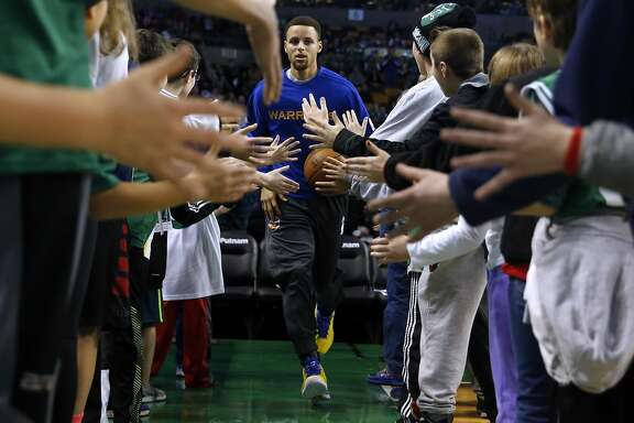 Golden State Warriors' Stephen Curry runs through Boston Celtics' fans before Warriors 124-119 double overtime win in NBA game at TD Garden in Boston, Massachusetts on Friday, December 11, 2015.