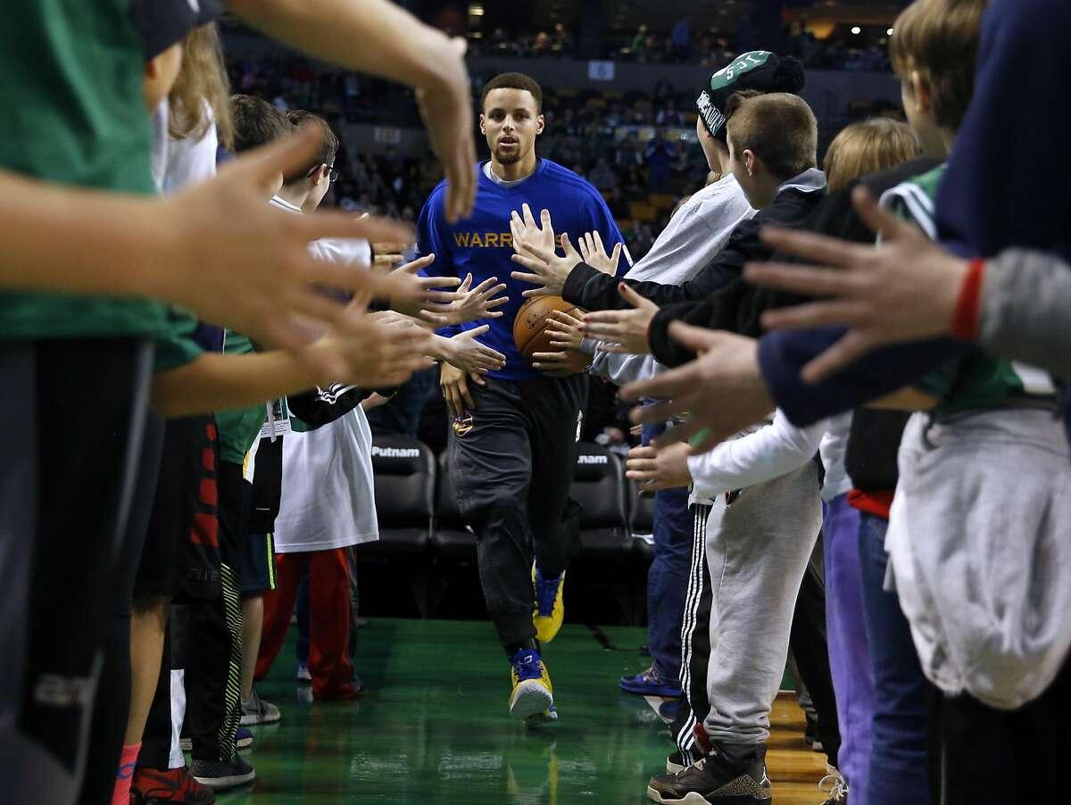 Golden State Warriors' Stephen Curry runs through Boston Celtics' fans before Warriors 124-119 double overtime win in NBA game at TD Garden in Boston, Massachusetts on Friday, December 11, 2015.