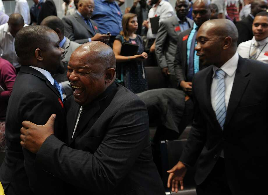 "Opposition party members celebrate the outcome of the Constitutional Court in Johannesburg Thursday, March 31, 2016.  The court ruled that President Jacob Zuma ""failed to uphold"" the law when he did not pay back some state funds used to upgrade his personal residence. (Felix Dlangamandla/Pool Photo via AP) Photo: Felix Dlangamandla, AP"