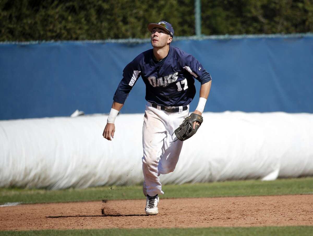 Lucas Erceg (17) runs in for a pop fly from his position at third base during Menlo College's game against Lewis-Clark State College in Atherton, California, on Wednesday, March 30, 2016.