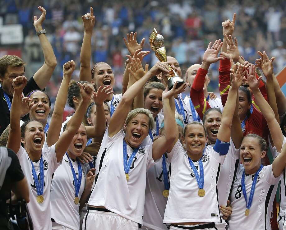 FILE - In this July 5, 2015, file photo, the United States Women's National Team celebrates with the trophy after they beat Japan 5-2 in the FIFA Women's World Cup soccer championship in Vancouver, British Columbia, Canada. Five players from the World Cup-winning U.S. national team have accused the U.S. Soccer Federation of wage discrimination in an action filed with the Equal Employment Opportunity Commission. Alex Morgan, Carli Lloyd, Megan Rapinoe, Becky Sauerbrunn and Hope Solo maintain in the EEOC filing they were paid nearly four times less than their male counterparts on the U.S. men's national team. The filing was announced Thursday in a statement from the law firm representing the players.  (AP Photo/Elaine Thompson, File) Photo: Elaine Thompson, AP
