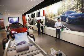 An employee assists a customer with pre-ordering the Tesla Motor Inc. Model 3 ahead of the announcement outside a store on the Third Street Promenade in Santa Monica, California, U.S., on Thursday, March 31, 2016. Tesla Motor Inc.'s first mass-production electric car, the Model 3, will be introduced on Thursday evening. Early buyers might save as much as $7,500 off the $35,000 sticker price of the Model 3. Photographer: Patrick T. Fallon/Bloomberg