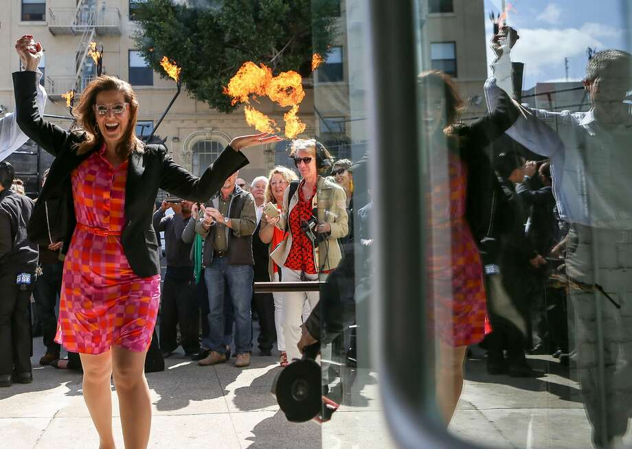 """Oakland Mayor Libby Schaaf excited walks hand in hand with Flax owner, Howard Flax, into the store after the  """"cutting of the iron bar"""" to commemorate the opening of the Flax Art and Design in Oakland on Thursday, March 31, 2016. Mayor Schaaf arrived in an art car motorcade which included """"Chester"""" the fire breathing horse art car. Photo: Amy Osborne, Special To The Chronicle"""