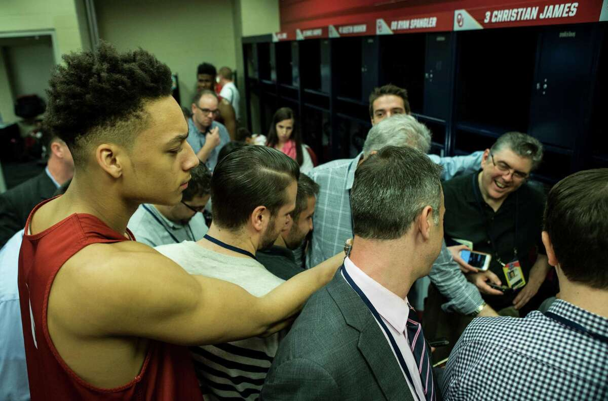 Oklahoma center Jamuni McNeace (4) reaches his phone into the media huddle surrounding teammate Buddy Hield in the locker room at NRG Stadium on Thursday, March 31, 2016, in Houston.