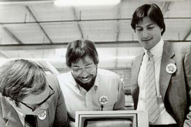 "July 18, 1983 - Apple Computer, Inc., announced the start of the first shipment of 9,000 computers to virtually every school in the state of California in a massive giveaway aimed at promoting ""computer literacy"" in the primary and secondary schools. The first and millionth produced were given to the Sunnyvale School District. Owen Whetzel, president of the school board, left, takes a close look at the computer. Steve Wozniak, co-founder, center,  and Steve Jobs, Chairman of the board of Apple Computer, Inc. is at right."