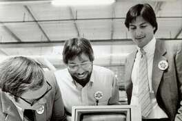 """July 18, 1983 - Apple Computer, Inc., announced the start of the first shipment of 9,000 computers to virtually every school in the state of California in a massive giveaway aimed at promoting """"computer literacy"""" in the primary and secondary schools. The first and millionth produced were given to the Sunnyvale School District. Owen Whetzel, president of the school board, left, takes a close look at the computer. Steve Wozniak, co-founder, center,  and Steve Jobs, Chairman of the board of Apple Computer, Inc. is at right."""