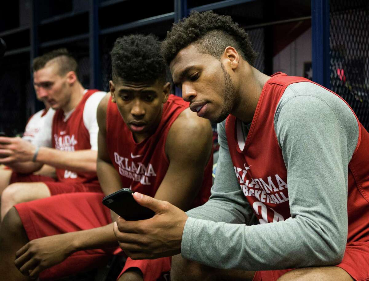 Oklahoma guard Christian James (3) and Oklahoma guard Buddy Hield (24) look on a phone as they sit in the locker room following practice for the NCAA national semifinal at NRG Stadium on Thursday, March 31, 2016, in Houston.