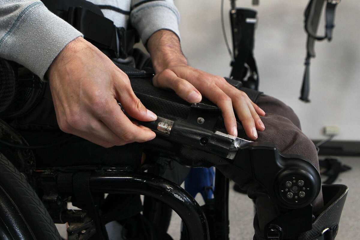 Steve Sanchez, who was paralyzed from the waist down in a BMX accident, clips his leg braces into the upper body segment of the Phoenix device, the latest robotics suit from SuitX, before test walking it at their offices in Berkeley, Calif., on Thursday March 31, 2016. This suit allows people who have been paralyzed, or have limited mobility, to walk again. This latest suit technology is considered to be the lightest and cheapest at $40,000.