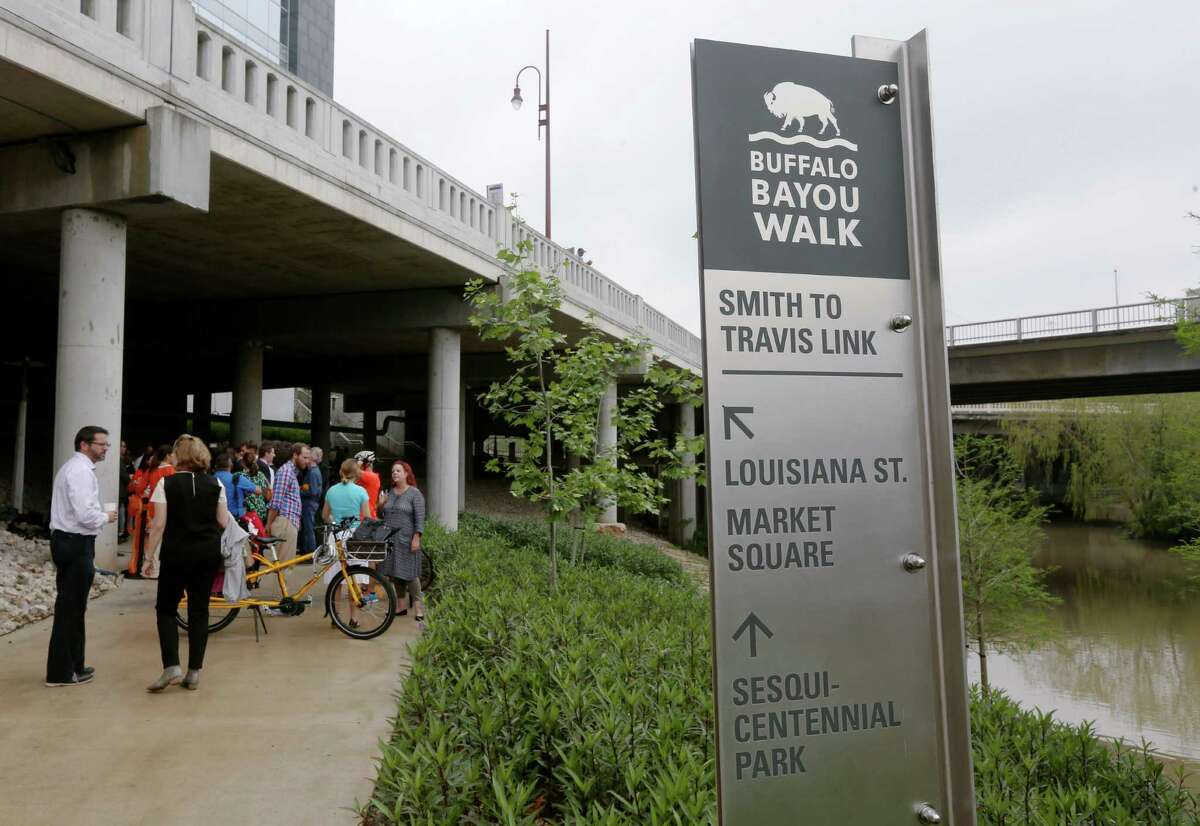 People gather along the new Buffalo Bayou Path between Smith Street and Travis Street, after a press conference and ribbon cutting ceremony, Thursday, March 31, 2016, in Houston.