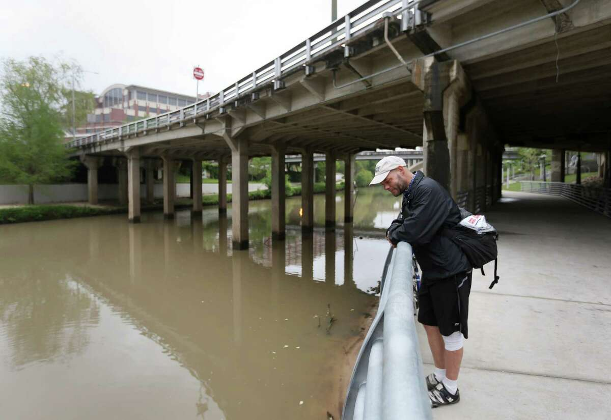 Chris Beaver, a bike messenger, feeds bread to baby ducks along the new Buffalo Bayou Path between Smith Street and Travis Street, March 31, 2016, in Houston.