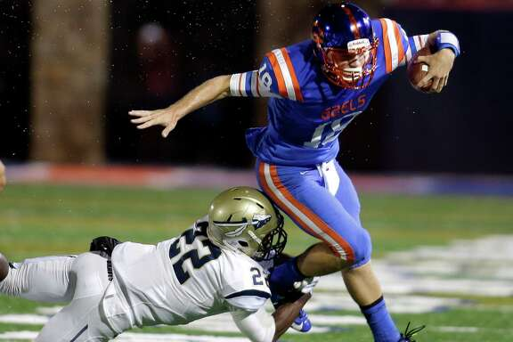 Bishop Gorman quarterback Tate Martell is tackled by St. John Bosco's Clifford Simms during the first half of a high school football game in Las Vegas on Sept. 26, 2014.
