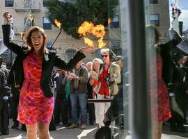 """Oakland Mayor Libby Schaaf excited walks hand in hand with Flax owner, Howard Flax, into the store after the  """"cutting of the iron bar"""" to commemorate the opening of the Flax Art and Design in Oakland on Thursday, March 31, 2016. Mayor Schaaf arrived in an art car motorcade which included """"Chester"""" the fire breathing horse art car."""