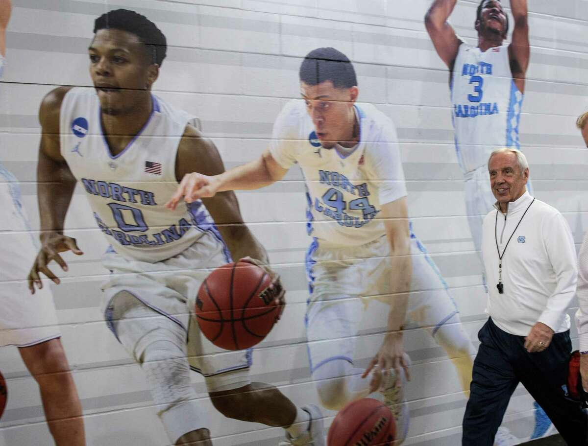 North Carolina head coach Roy Williams walks past image of his players following practice for the NCAA national semifinal at NRG Stadium on Thursday, March 31, 2016, in Houston.