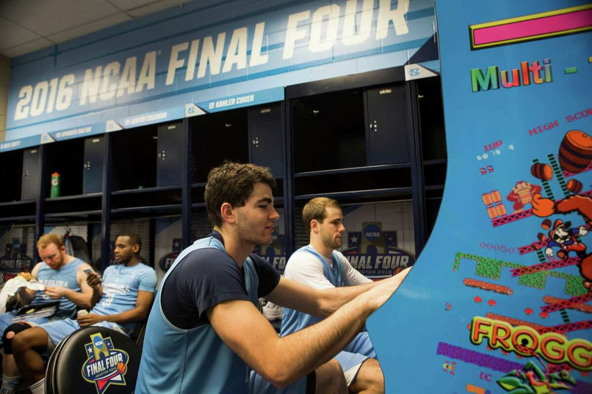 North Carolina forward Luke Maye, left, and guard Kanler Coker play video games in the locker room following practice for the NCAA national semifinal at NRG Stadium on Thursday, March 31, 2016, in Houston.