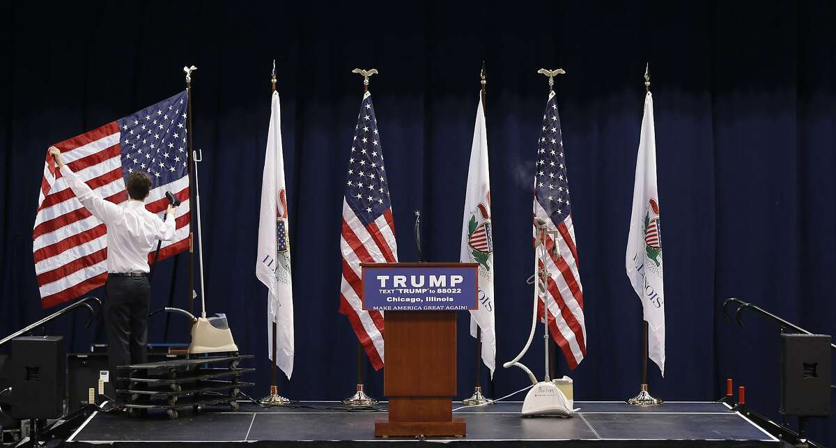 A member of Republican presidential candidate, Donald Trump's campaign staff, removes wrinkles from an American flag before a rally on the University of Illinois-Chicago campus, Friday, March 11, 2016, in Chicago. (AP Photo/Charles Rex Arbogast)