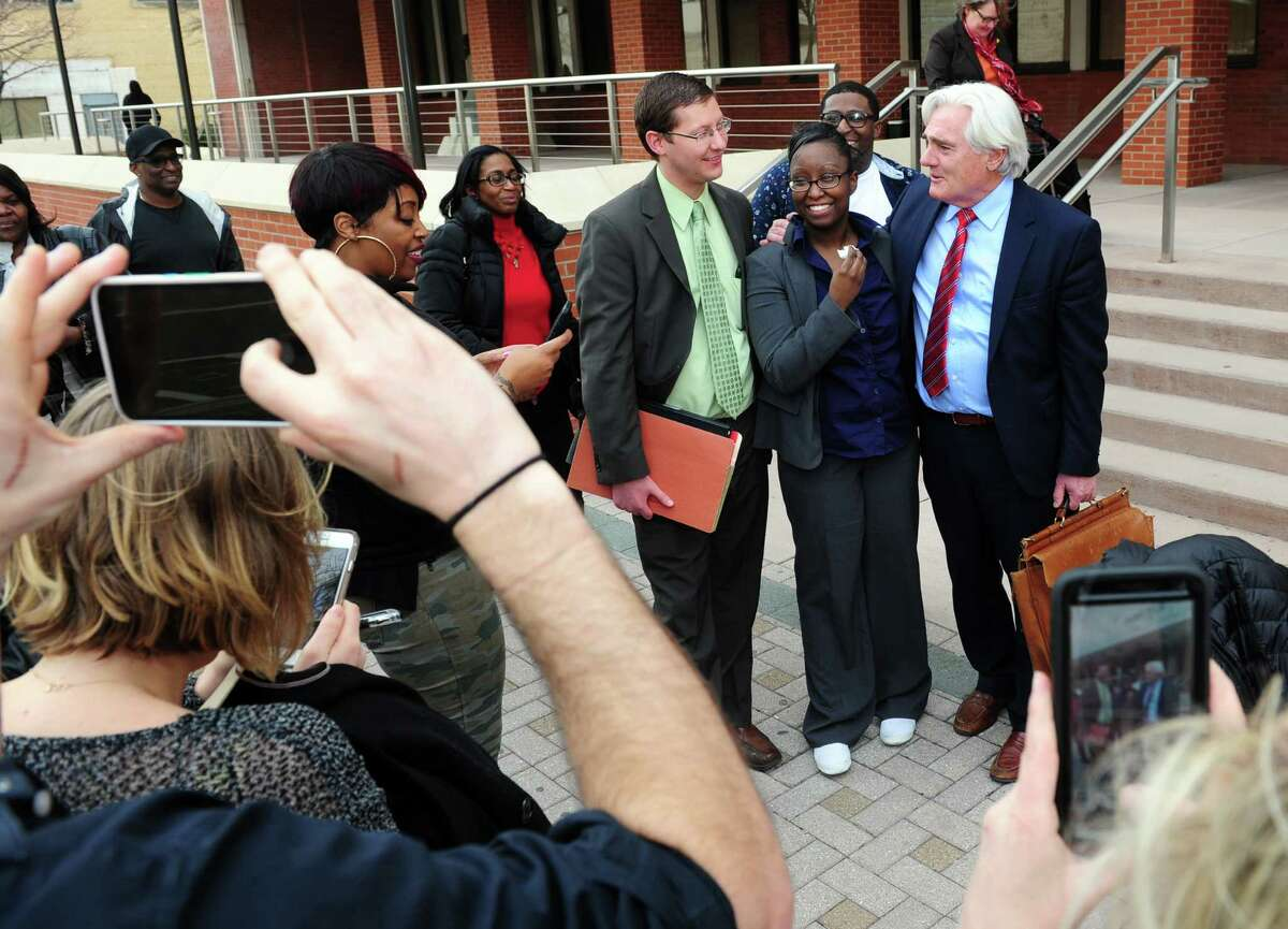 Cherelle Baldwin, a young mother who claims she crushed her abusive boyfriend Jeffrey Brown with her car in self-defense, poses with her attorneys Matthew Popilowski and Miles Gerety, at right, after being found not guilty at Superior Court on Main Street in Bridgeport, Conn., on Thursday Mar. 31, 2016.