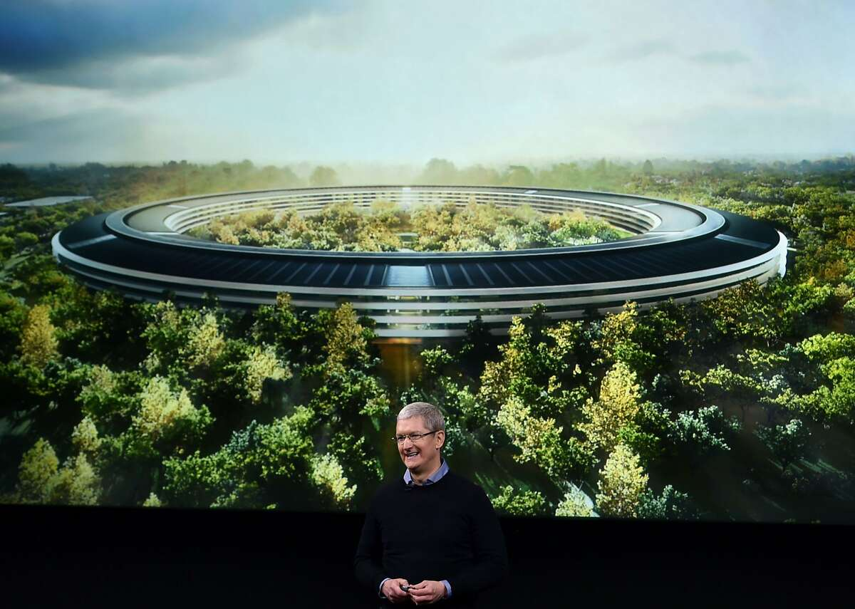 Apple CEO Tim Cook stands in front of a slide of the company's new campus which is under construction during a media event at Apple headquarters in Cupertino, California on March 21, 2016. / AFP PHOTO / Josh EdelsonJOSH EDELSON/AFP/Getty Images