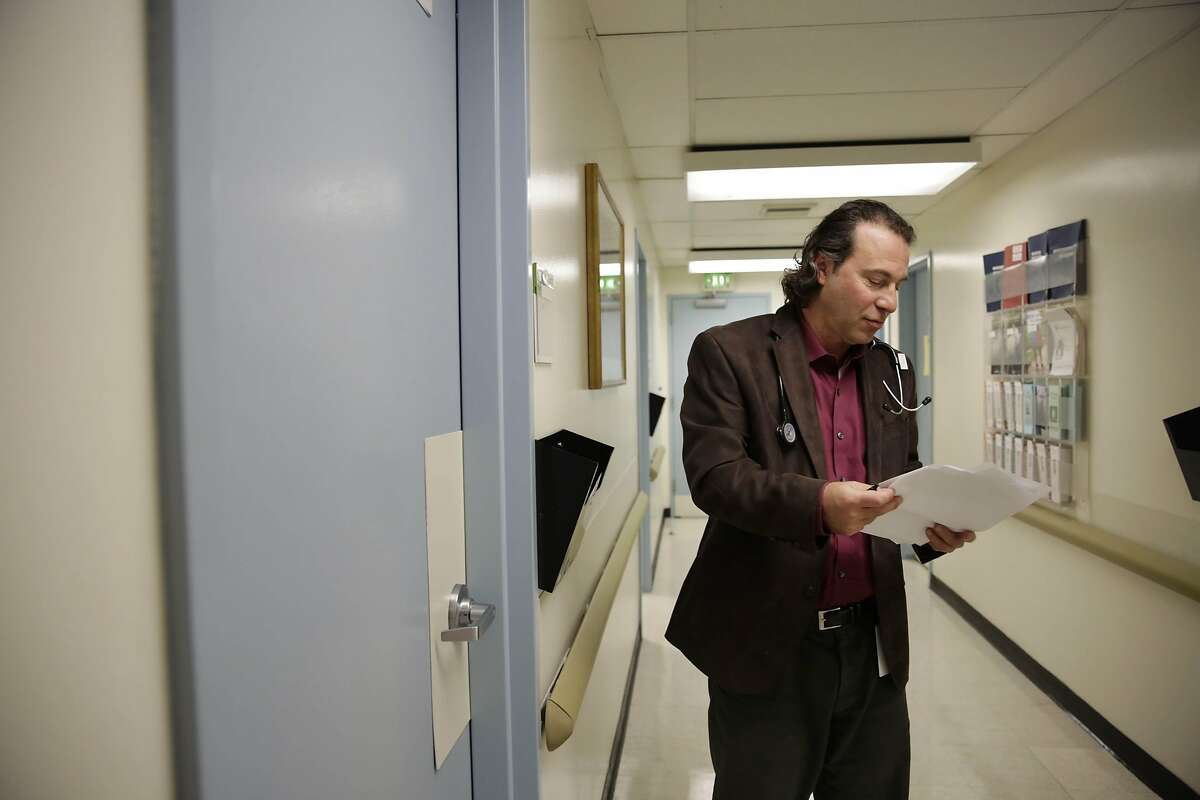 Dr. Dean Schillinger organizes paperwork in the corridor before meeting a patient at San Francisco General Hospital on Monday, February 22, 2016 in San Francisco, California.