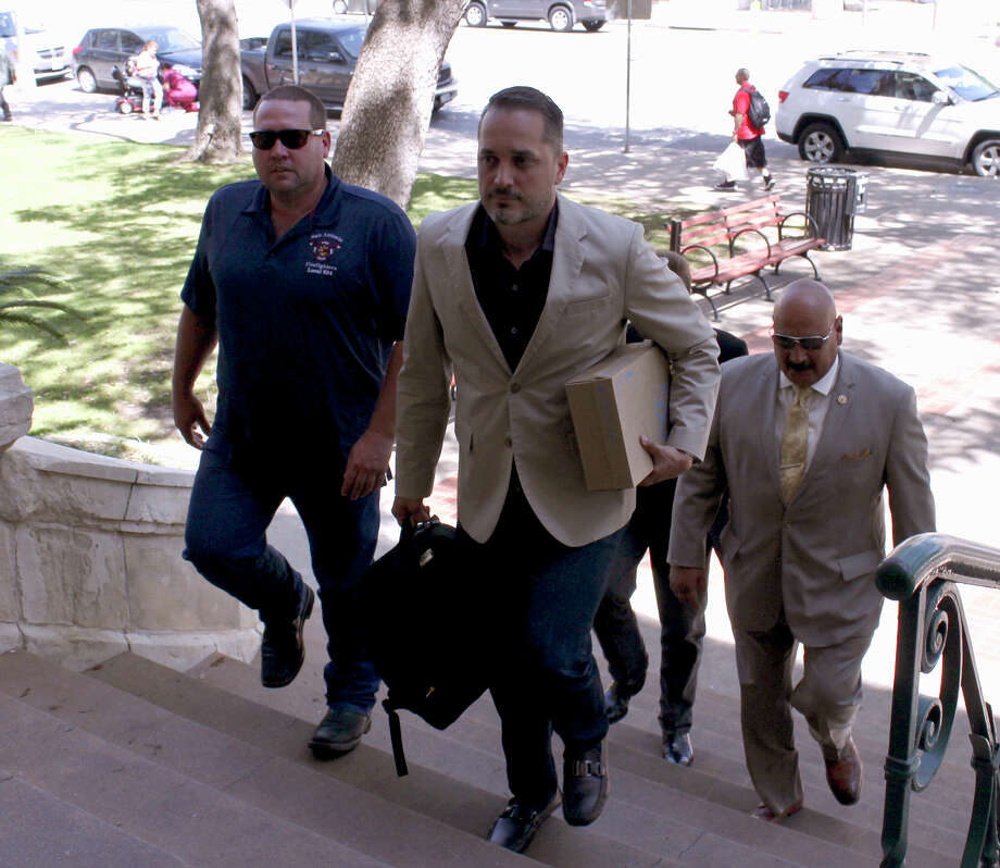 L to R: Stephen Moody, Greg Brockhouse and Rudy Morales deliver signatures in a petition opposing San Antonio Water System rate hikes to City Hall on Thursday. Photo: Brendan Gibbons / San Antonio Express-News / San Antonio Express-News