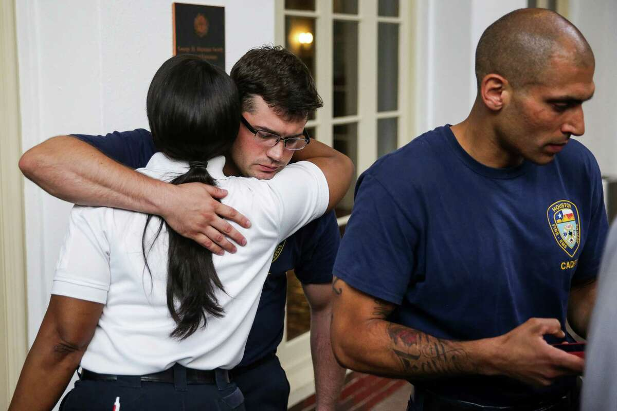 Houston Fire Department Cadet Michael Smith receives a hug from HFD Assistant Fire Chief Lisa Campbell after a press conference onWhitfield's death onThursday.
