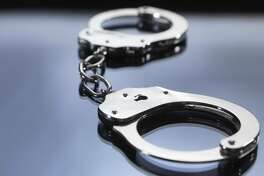 File photo of handcuffs on table. Close up of metal handcuffs