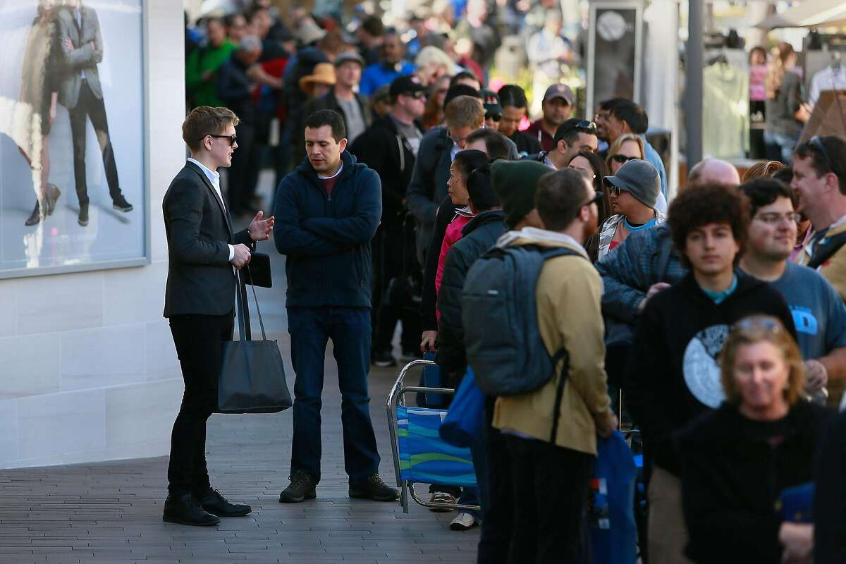 A Tesla product specialist, left, speaks with prospective Tesla Model 3 owners waiting in line to place a deposit on the new electric car model, expected to go into production next year, in La Jolla, Calif., on Thursday, March 31, 2016. (Misael Virgen/San Diego Union-Tribune/TNS)