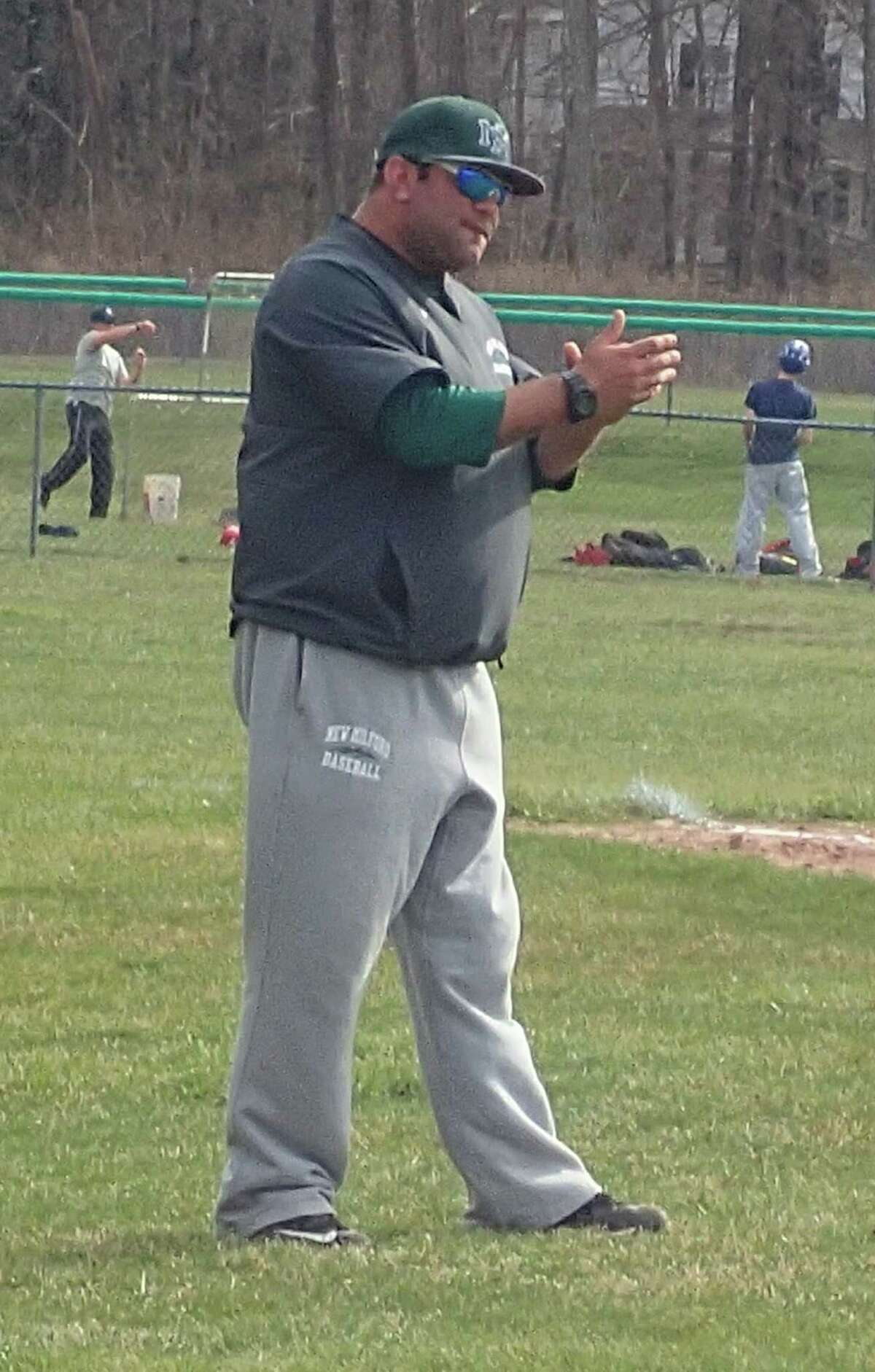 New Milford baseball coach Ryan Johnson encourages one of his hitters from the third-base coach's box during the Green Wave's scrimmage with Shepaug at Ted Alex Field in Washington March 31, 2016.