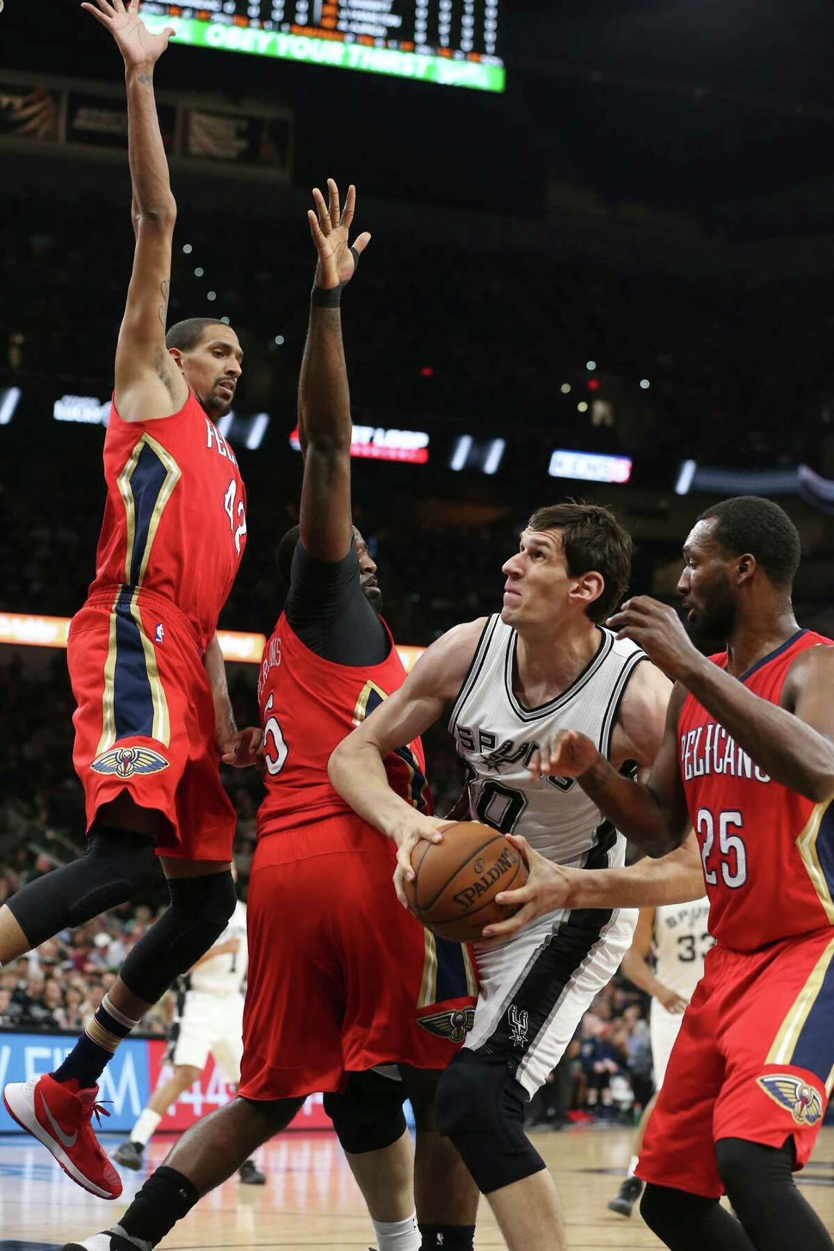 San Antonio Spurs' Boban Marjanovic looks to get through New Orleans Pelicans' Alexis Ajinca, from left, Kendrick Perkins and Jordan Hamilton during the first half at the AT&T Center, Wednesday, March 30, 2016.