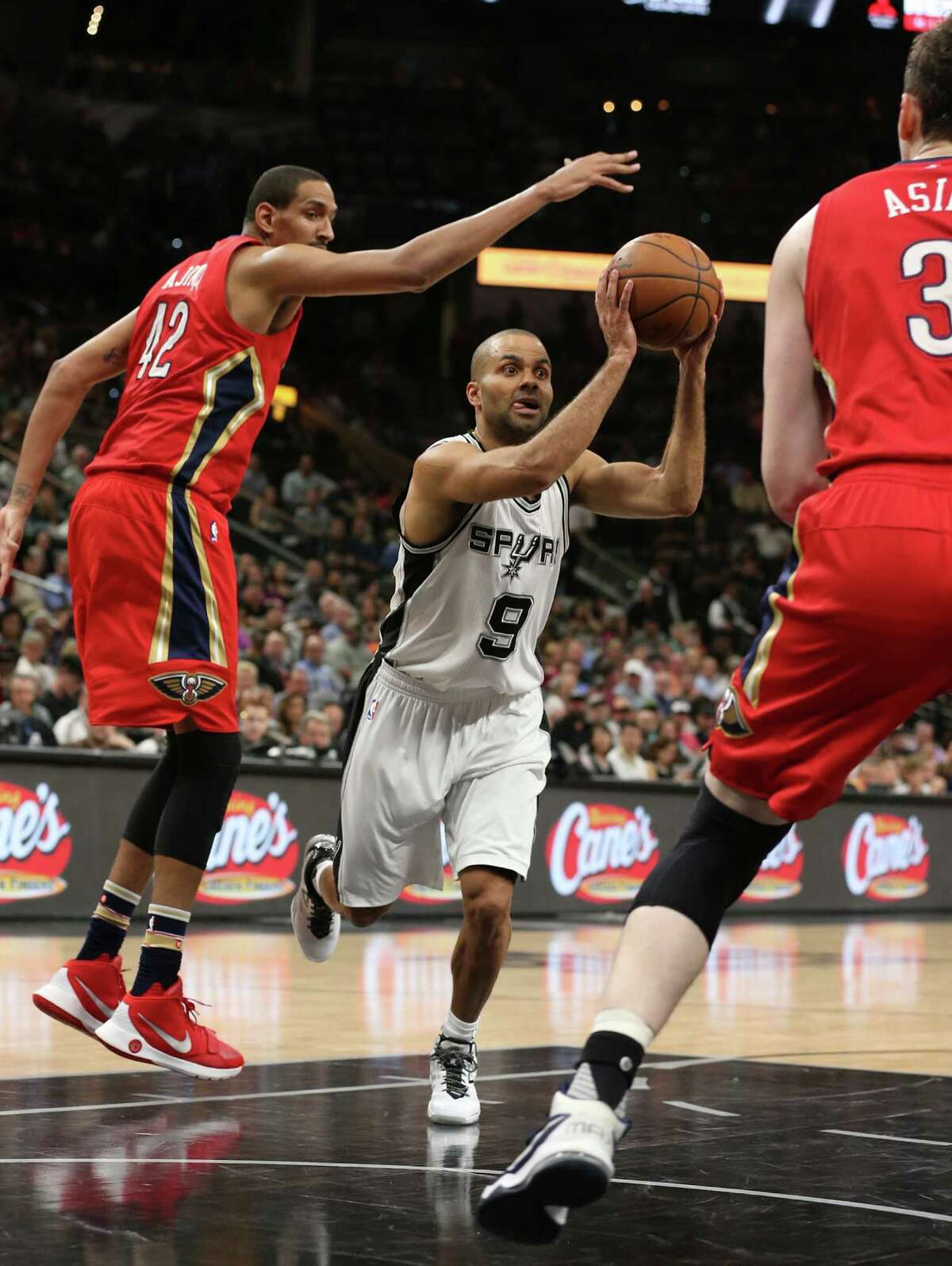 San Antonio Spurs' Tony Parker looks to pass the ball between New Orleans Pelicans' Alexis Ajinca, left, and New Orleans Pelicans' Omer Asik during the first half at the AT&T Center, Wednesday, March 30, 2016.