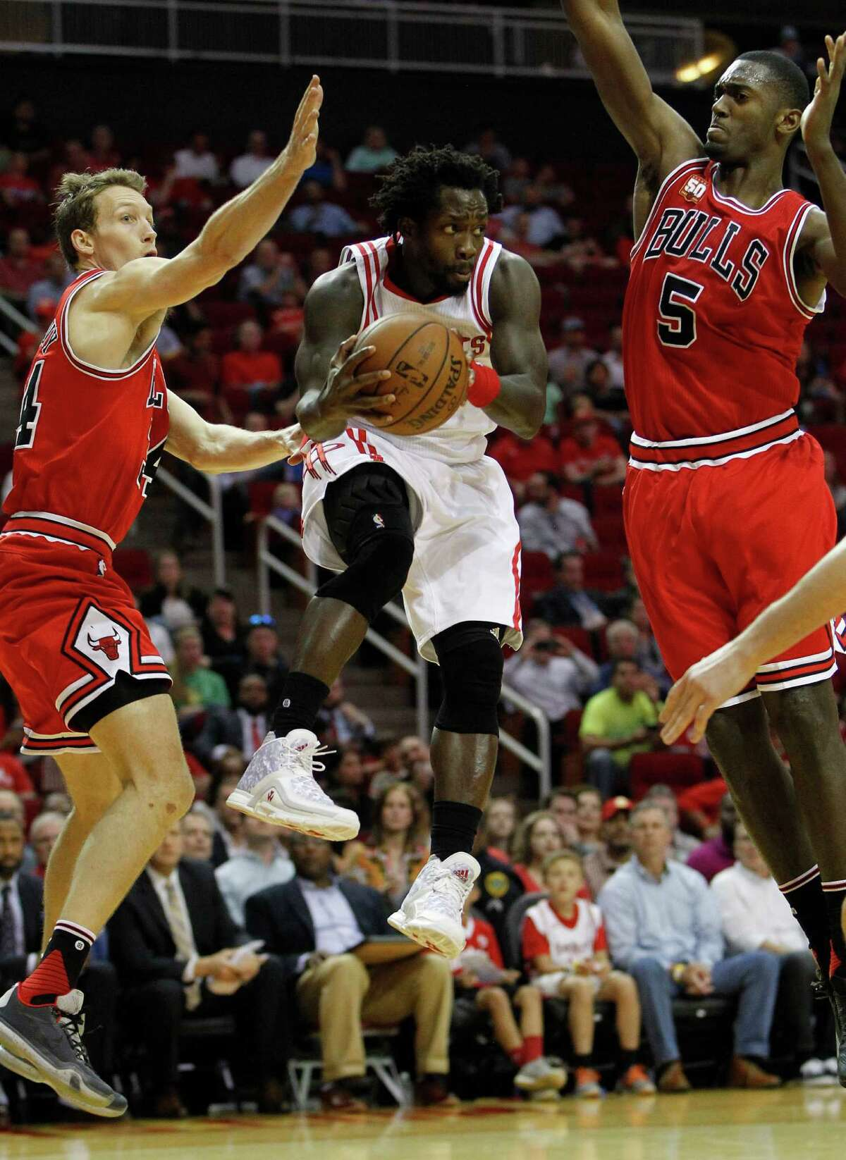 Houston Rockets guard Patrick Beverley (2) tries to pass off the ball between Chicago Bulls guard Mike Dunleavy (34) and orward Bobby Portis (5) during the first half of an NBA basketball game at Toyota Center, Thursday, March 31, 2016, in Houston.