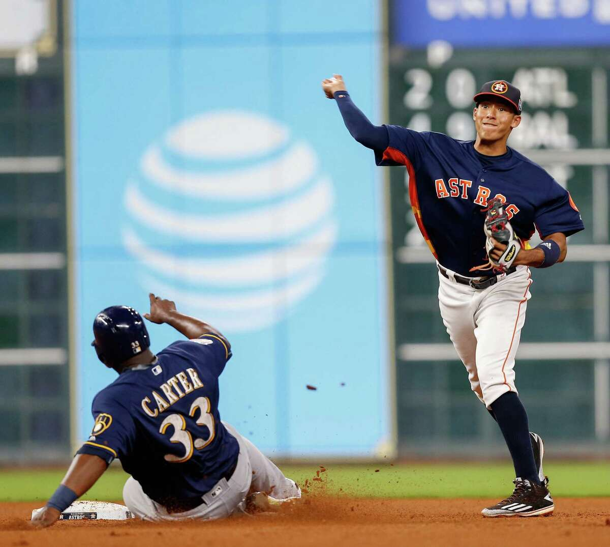 Houston Astros' Carlos Correa (1) throws to first base to complete a double play in the second inning as Milwaukee Brewers' Chris Carter (33) slides into second base during a spring training baseball game Thursday, March 31, 2016, in Houston.