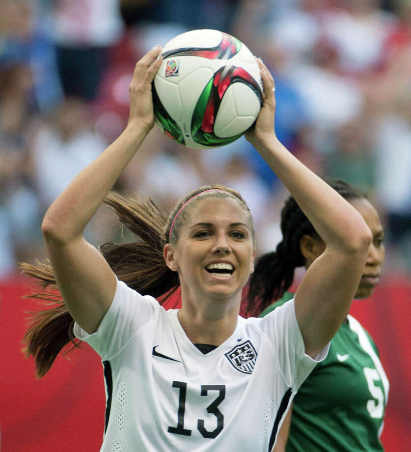 FILE -  In  this June 16, 2015, file photo,  United States' Alex Morgan celebrates teammate Abby Wambach's goal as Nigeria's Onome Ebi looks on during the first half of a FIFA Women's World Cup soccer match in Vancouver, British Columbia, Canada. Five players from the World Cup-winning U.S. national team have accused the U.S. Soccer Federation of wage discrimination in an action filed with the Equal Employment Opportunity Commission. Alex Morgan, Carli Lloyd, Megan Rapinoe, Becky Sauerbrunn and Hope Solo maintain in the EEOC filing they were payed nearly four times less than their male counterparts on the U.S. men's national team. The filing was announced in a press release on Thursday, March 31, 2016.  (Jonathan Hayward/The Canadian Press via AP, File) MANDATORY CREDIT ORG XMIT: NY153 Photo: Jonathan Hayward / CP