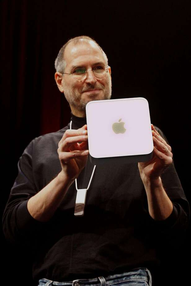 Steve Jobs unveils the new Mac Mini G4, while wearing the new iPod Shuffle around his neck after giving the keynote address during the Macworld Conference in San Francisco on Tuesday, Jan. 11, 2005.  Photo: JEFF CHIU, Associated Press