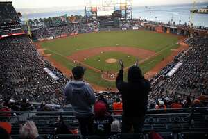 Fans cheer as the San Francisco Giants take the field to play the Oakland A's in the Bay Bridge Series at AT&T Park in San Francisco, Calif., on Thursday, March 31, 2016.