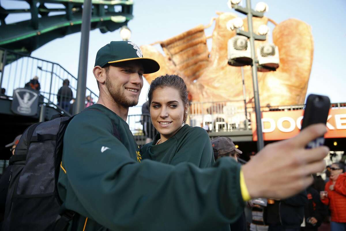 Oakland A's fans Bryce Brooks and Emilia Borkowski of La Mirada take a selfie before Athletics play the San Francisco Giants in the first game of the Bay Bridge Series at AT&T Park in San Francisco, Calif., on Thursday, March 31, 2016.
